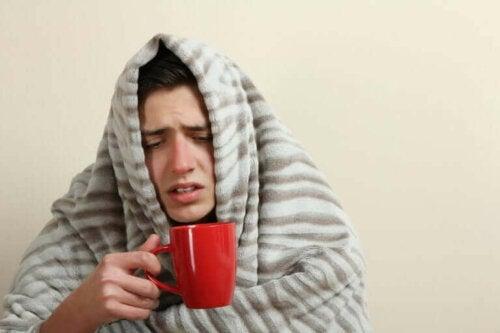 Een man zit onder een deken met een kop thee