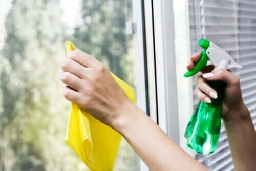 Een vrouw die de ramen schoonmaakt met groene schoonmaakmiddelen