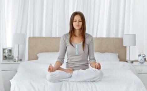 Een vrouw die in bed mediteert