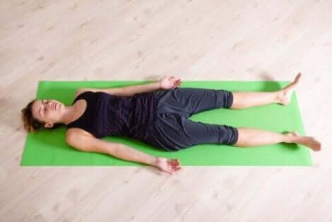 Een vrouw die op een yogamat ligt