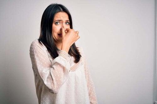 Vrouw houdt neus dicht tegen stank