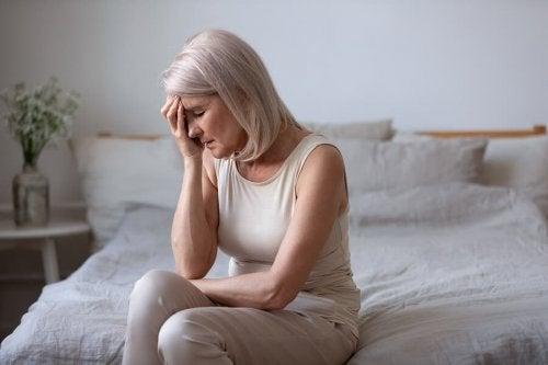 Vrouw zit met hoofdpijn op bed