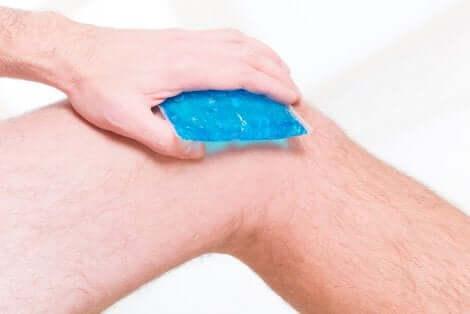 Een man die een ijspak op zijn knie aanbrengt