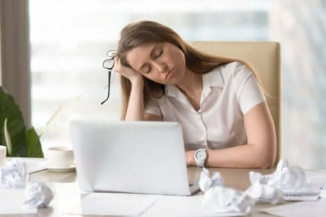 Een vrouw die achter haar computer in slaap valt