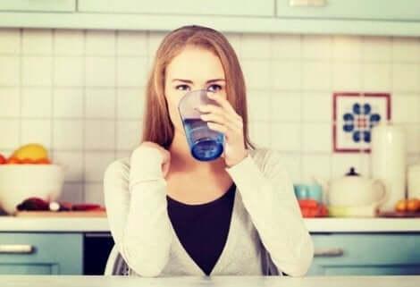 Een vrouw drinkt water om prediabetes onder controle te houden