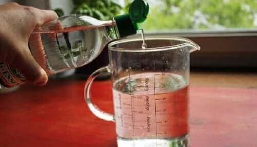 Witte azijn wordt in een beker gegoten.