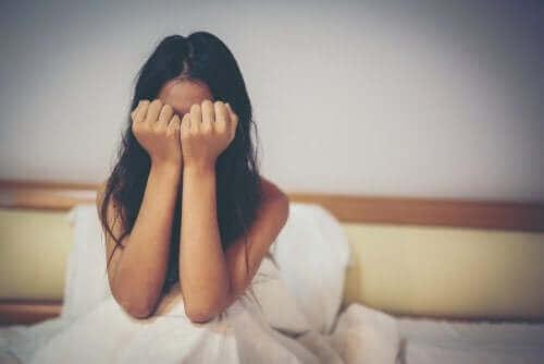Vrouw zit op bed te huilen