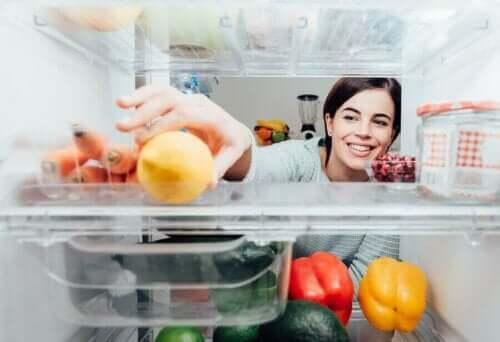 Vrouw pakt iets uit de koelkast