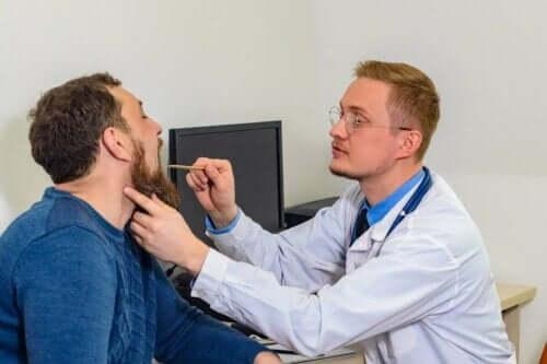 Een man die zijn stembanden laat controleren door een dokter