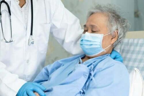 Een patiënt met mondkapje en een arts