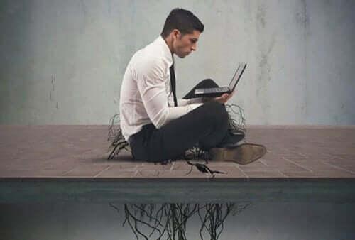 Man op laptop met wortels die hem op de grond houden