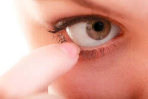 Vrouw wijst naar haar oog