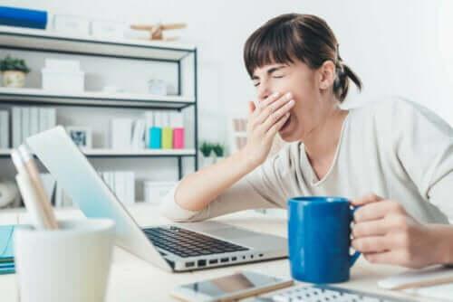 Vernoeide vrouw achter laptop