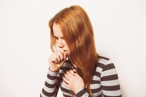 Een vrouw hoest en houdt haar hand voor haar mond