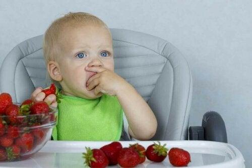 Een kind eet aardbeien