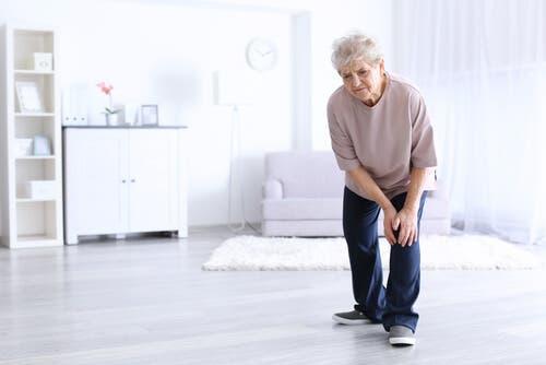 Een oudere vrouw grijpt naar haar knie