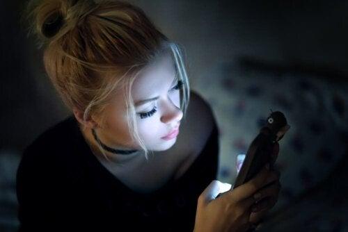 Een vrouw kijkt in het donker naar een beeldscherm