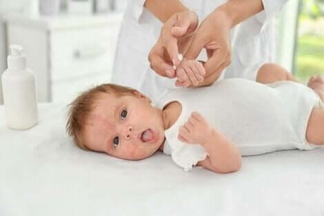 Een baby op aankleedkussen