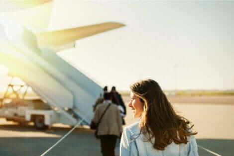 Een vrouw die in een vliegtuig stapt