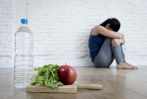 Vrouw eet alleen sla en wat water