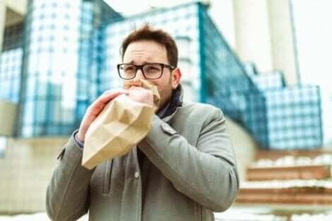 Een man ademt in een papieren zak