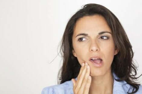 Een vrouw raakt haar kaak aan met haar hand