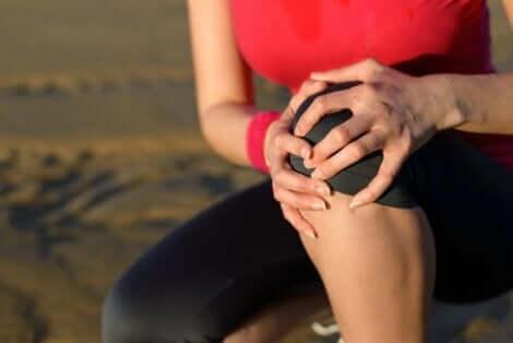 Een vrouw houdt haar handen tegen haar knie