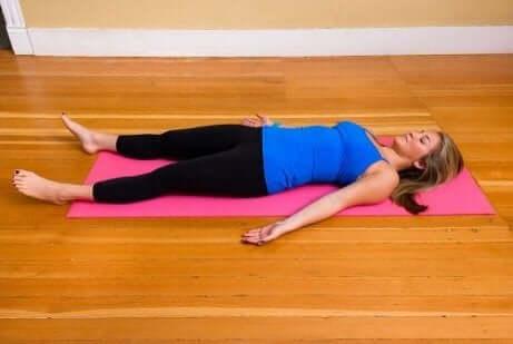 Een vrouw ligt op haar rug op een yogamat
