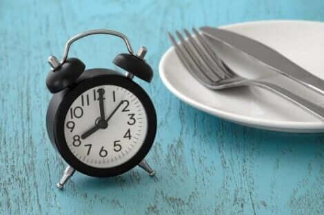 Een wekker op een tafel naast een bord en bestek