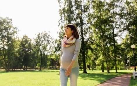 Een zwangere vrouw met een buikband wandelt in het park