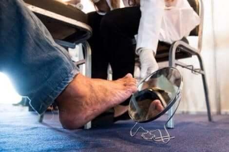 Een diabetespatiënt die zijn voet in de spiegel controleert