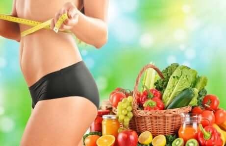Een vrouw staat voor een mand fruit en groenten met een meetlint om haar middel