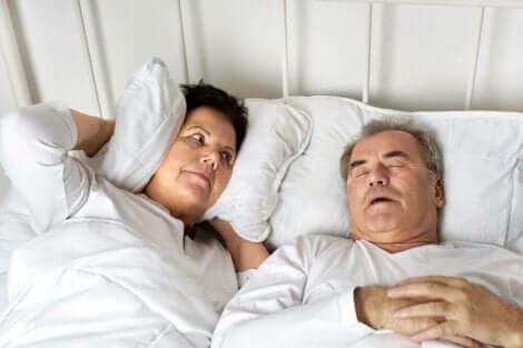 Een man snurkt in bed en zijn vrouw houdt een kussen tegen haar oren