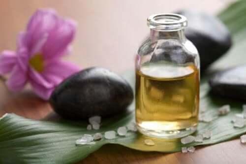 Een flesje etherische olie met een zwarte steen en een paarse bloem
