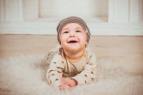 Een baby die op het tapijt kruipt