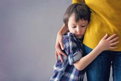 een jongen klampt zich vast aan zijn moeder