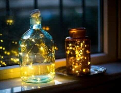 Lampen van glazen flessen bij een raam