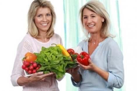 Twee vrouwen die groenten vasthouden