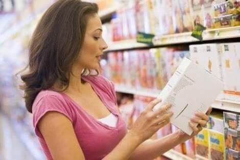 Vrouw leest productingrediënten in de supermarkt