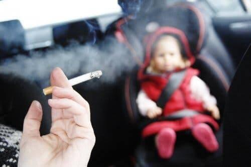Baby in een auto met iemand die rookt