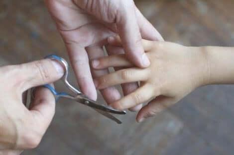 Nagels van een kind worden geknipt