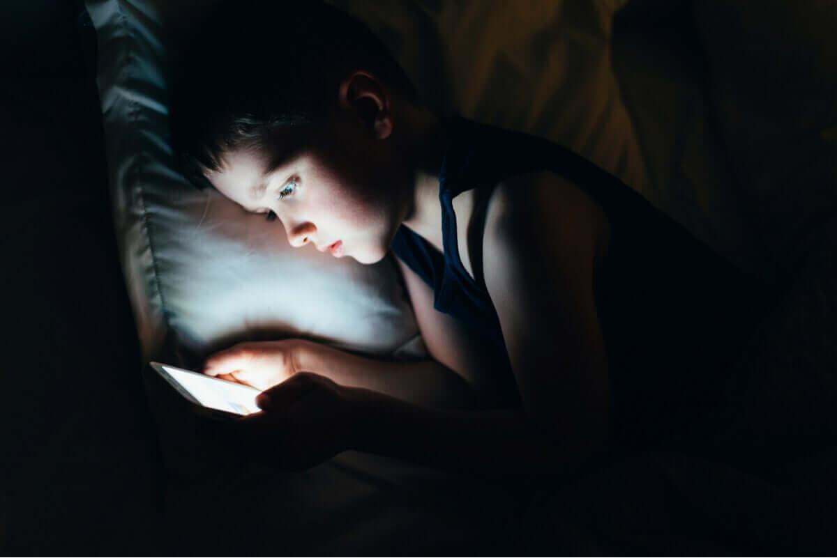 Kind zit in het donker op een tablet