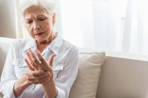 Vrouw bekijkt pijnlijke hand