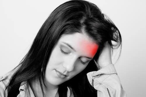 Vrouw houdt pijnlijke hoofd vast