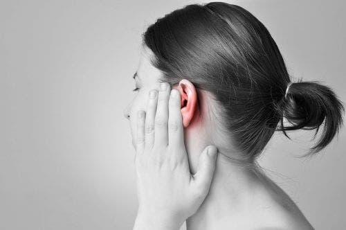 Vrouw met haar hand op pijnlijk oor