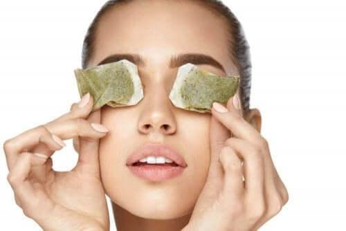 Vrouw met theezakjes op de ogen om pijnlijke ogen te verminderen