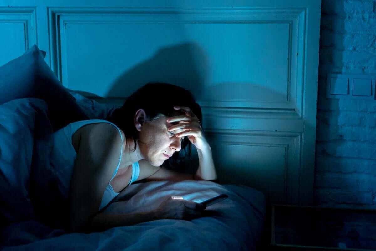 Vrouw zit in de nacht op haar mobiel