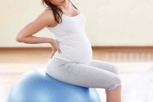 Een zwangere vrouw zit op een pilatesbal