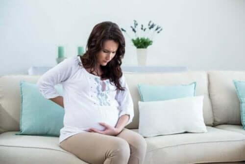 Een zwangere vrouw zit op de bank met haar hand tegen haar buik