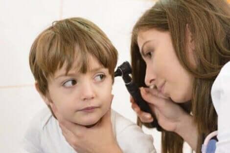 Een arts die de oorontsteking van een kind controleert